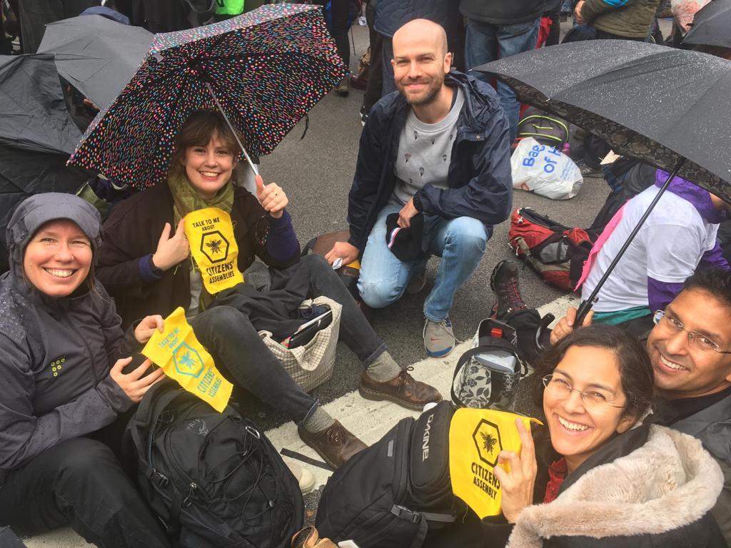 photograph of members of the XR Citizens' Assembly Working Group sitting in the road, holding umbrellas and bee and hive logo patches.